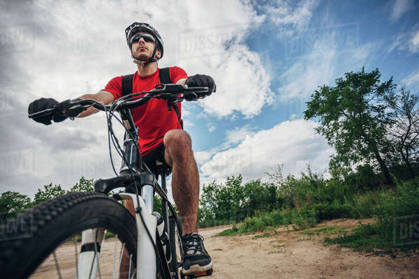 Low angle view of mountain biker riding on dirt road against sky Royalty-free stock photo