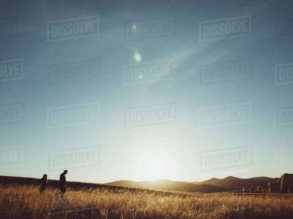 Couple walking on field against sky during sunny day Royalty-free stock photo