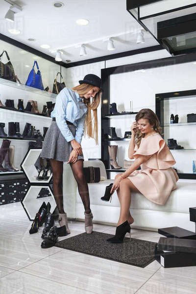 Happy female friends trying on shoes at store Royalty-free stock photo