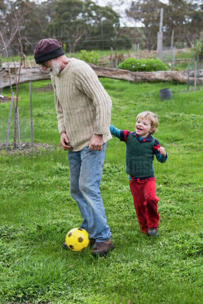 Full length of grandfather and grandson playing soccer on grassy field Royalty-free stock photo