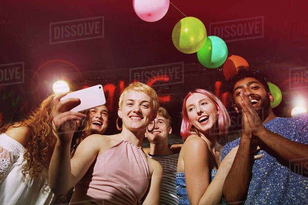 Low angle portrait of happy woman taking selfie with friends at yard Royalty-free stock photo