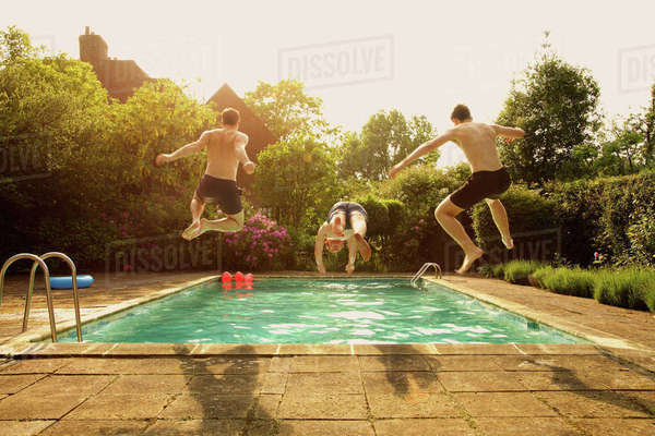 Rear view of men jumping in swimming pool during summer Royalty-free stock photo