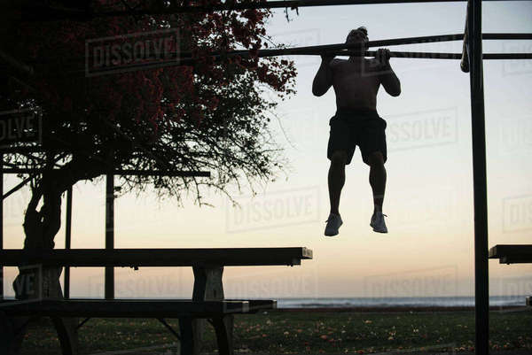 Full length of man doing chin-ups at park against sky at sunset Royalty-free stock photo
