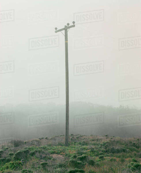 Electricity pylon on hill in foggy weather Royalty-free stock photo