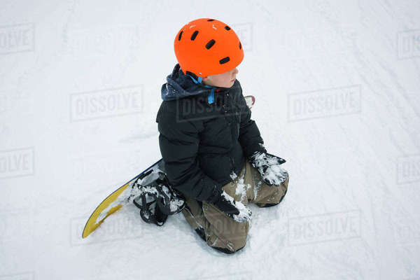 High angle view of boy with snowboard kneeling in snow Royalty-free stock photo