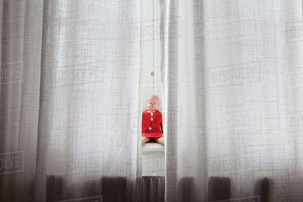 Doll sitting on windowsill behind curtains Royalty-free stock photo
