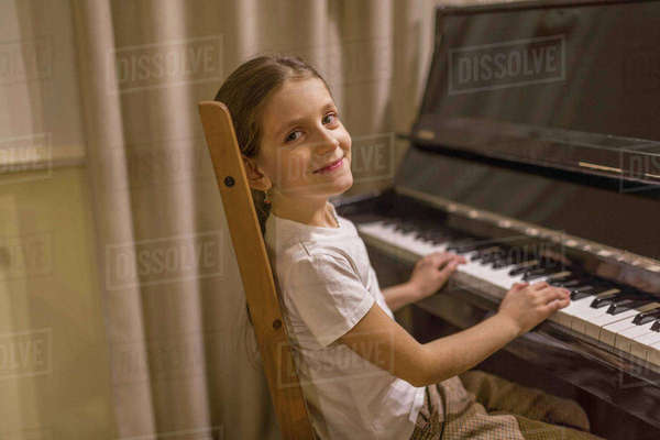 Side view portrait of cute girl playing piano at home Royalty-free stock photo