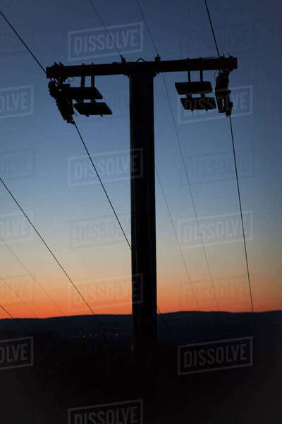 Low angle view of silhouette electricity pylon on field against sky during sunset Royalty-free stock photo
