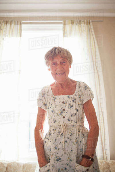 Portrait of happy senior woman sanding at brightly lit home Royalty-free stock photo
