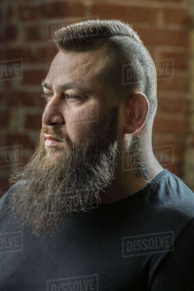 Close-up of male hairdresser with beard and tattoo looking away at barber shop Royalty-free stock photo