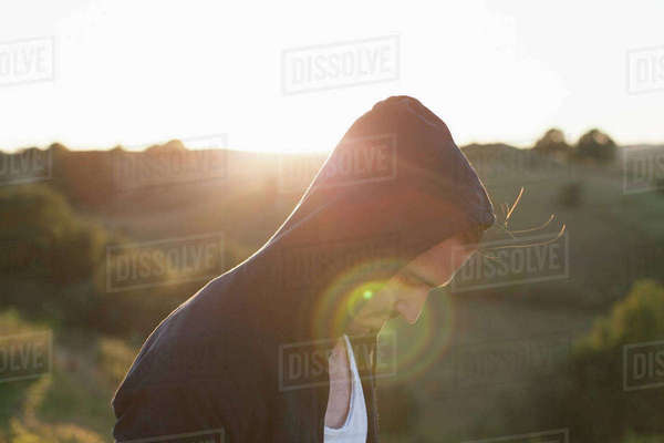 Side view of man wearing hooded jacket on field during sunny day Royalty-free stock photo