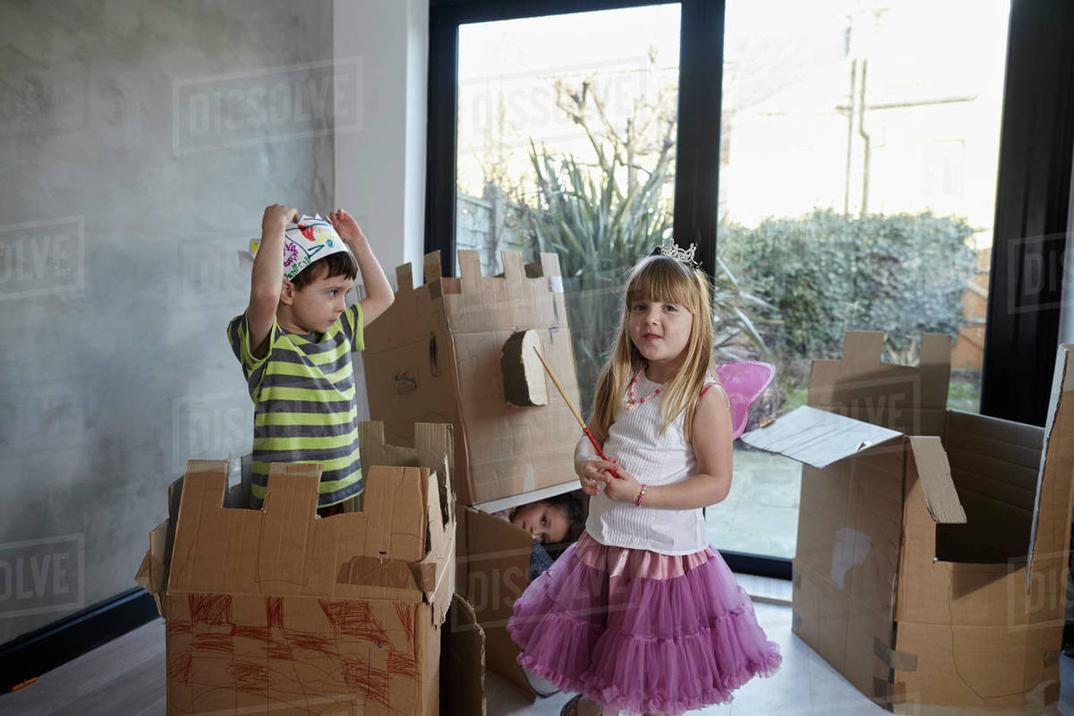 Children wearing costume playing with cardboard boxes against window Royalty-free stock photo