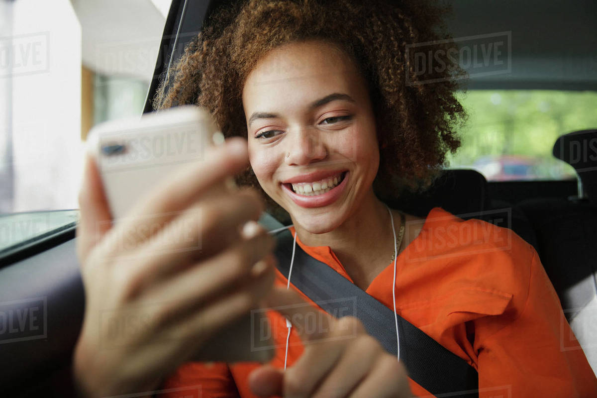 Smiling young woman using smart phone in car Royalty-free stock photo