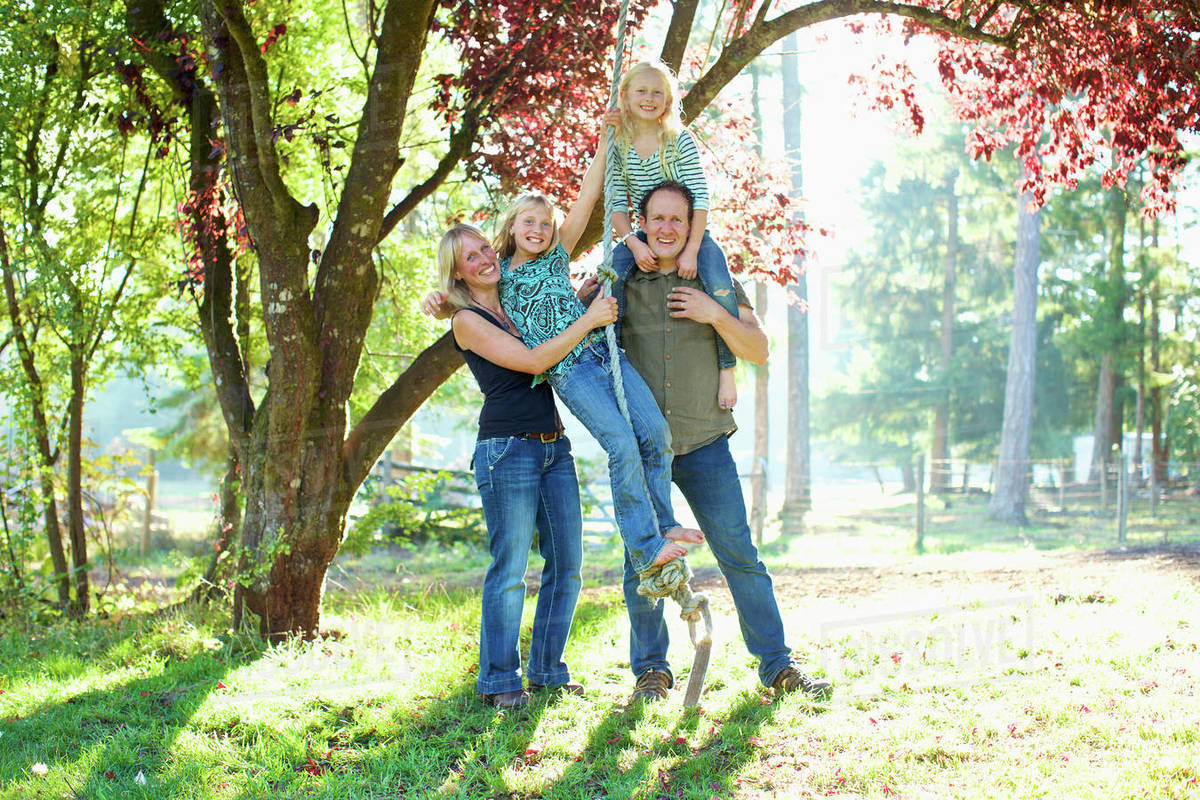 Portrait happy family on rope swing in sunny autumn park Royalty-free stock photo