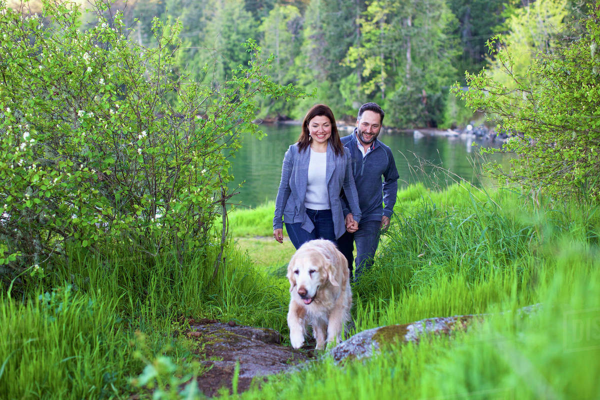 Happy couple with dog hiking along lush green lakeside, Mill Bay, British Columbia, Canada Royalty-free stock photo