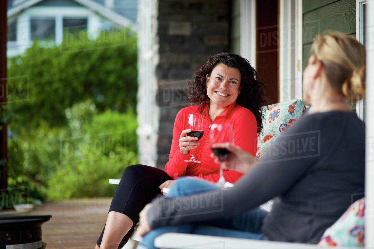 Happy women talking and drinking red wine on front porch Royalty-free stock photo