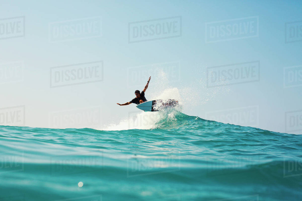 Male surfer riding turquoise blue ocean wave Royalty-free stock photo