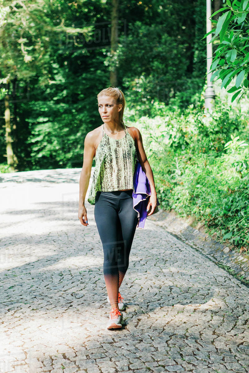 Fit female personal trainer walking on cobblestone path in park Royalty-free stock photo