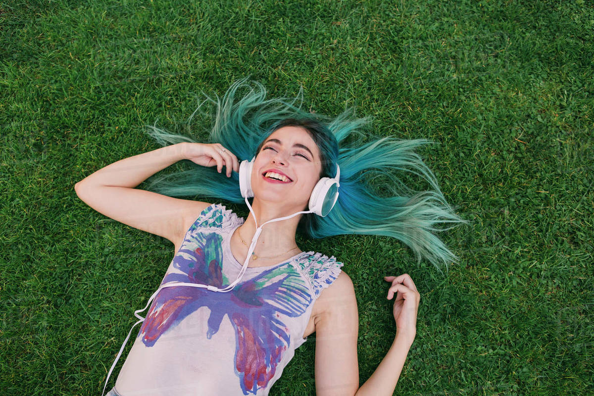Happy, carefree young woman with blue hair listening to music with headphones, laying in grass Royalty-free stock photo