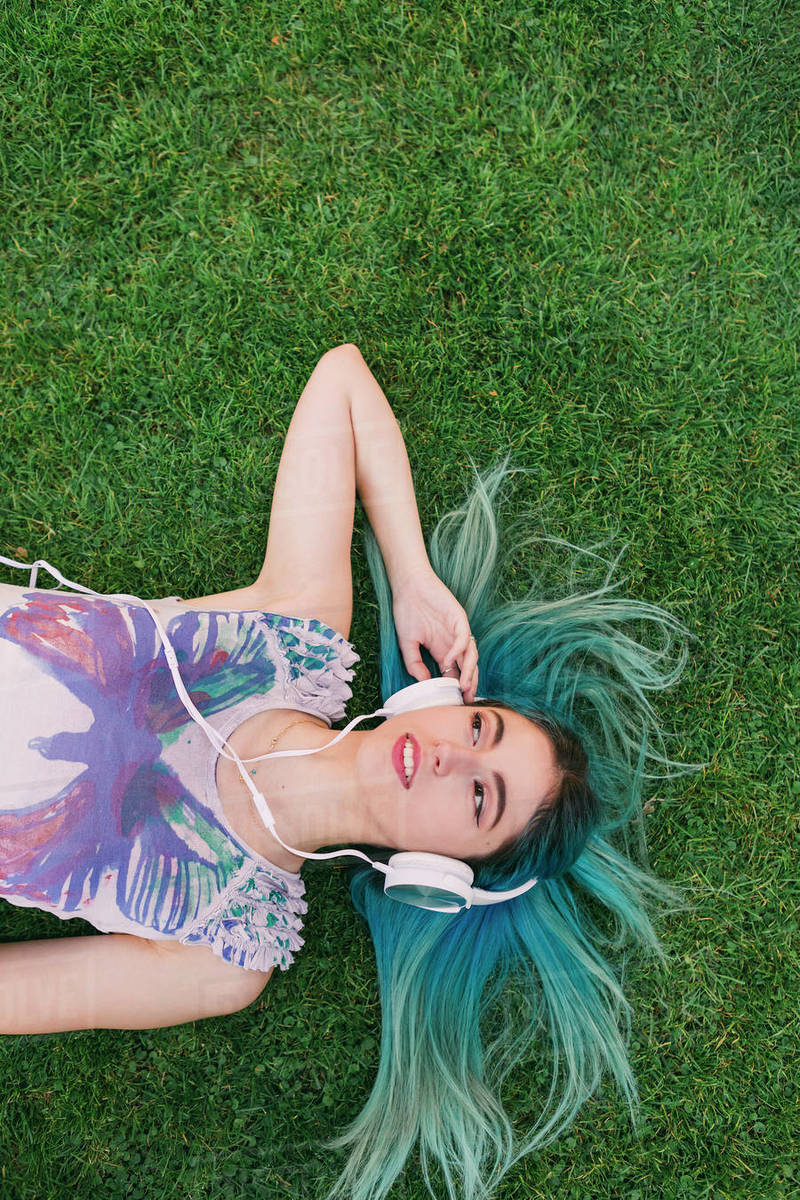 Overhead portrait young woman with blue hair listening to music with headphones, laying in grass Royalty-free stock photo