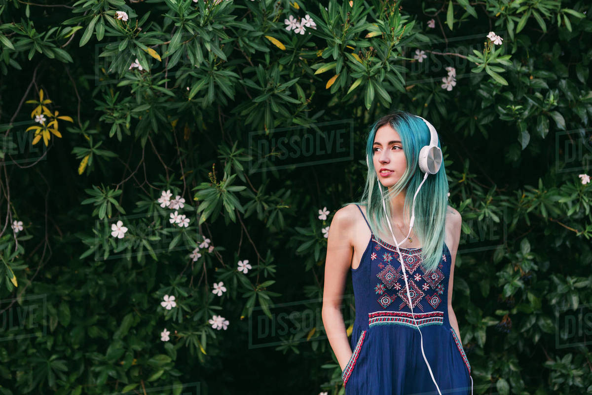 Young woman with blue hair listening to music with headphones in front of flowering tree Royalty-free stock photo