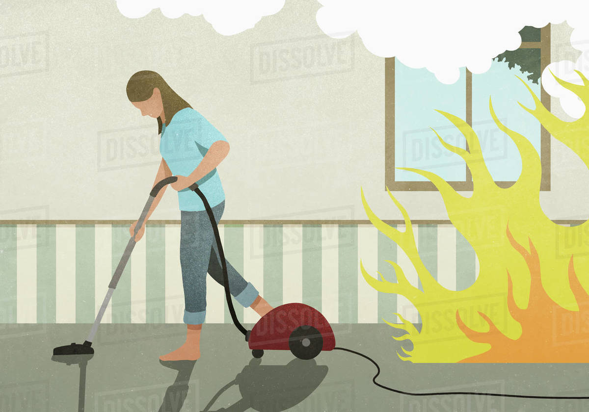 Flames and smoke behind oblivious woman vacuuming carpet Royalty-free stock photo
