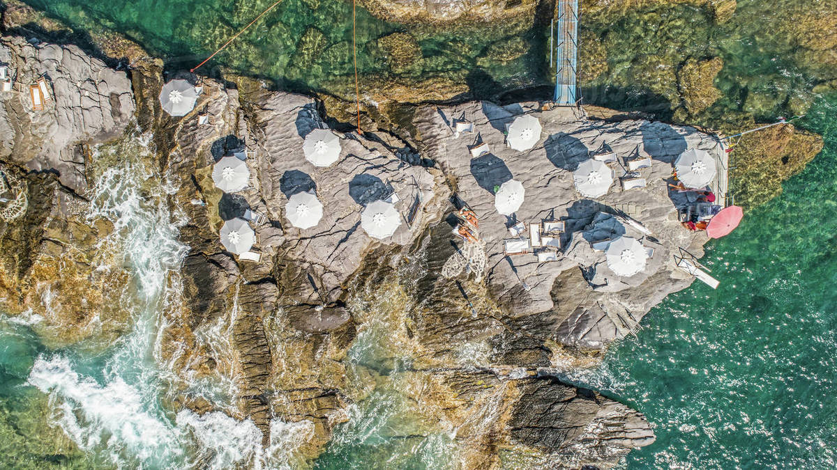 Aerial view from above beach umbrellas on sunny rocks above ocean, Nervi, Italy Royalty-free stock photo