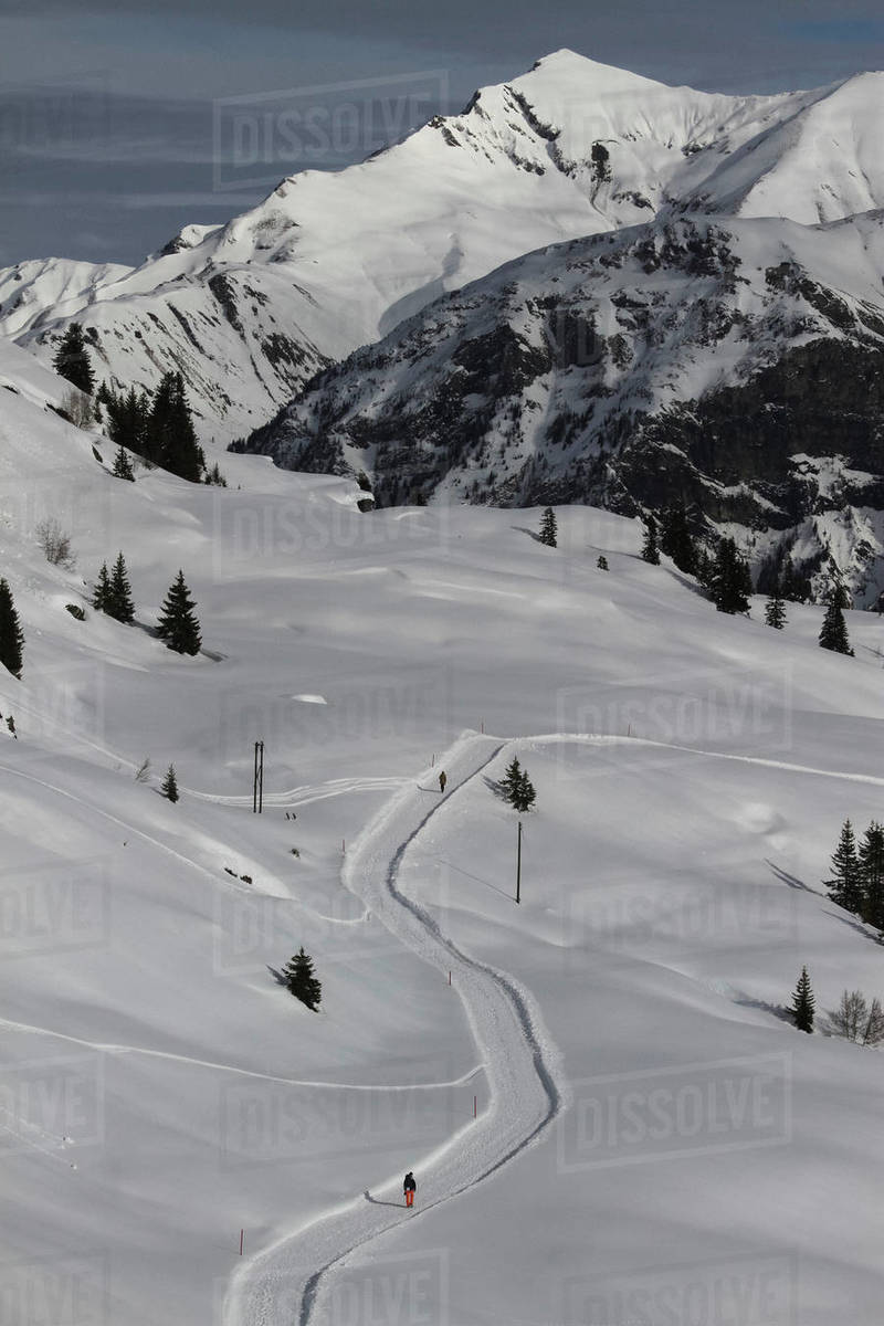 Snowshoers on sunny, snowy mountain path, Vals, Canton of Grisons, Switzerland Royalty-free stock photo