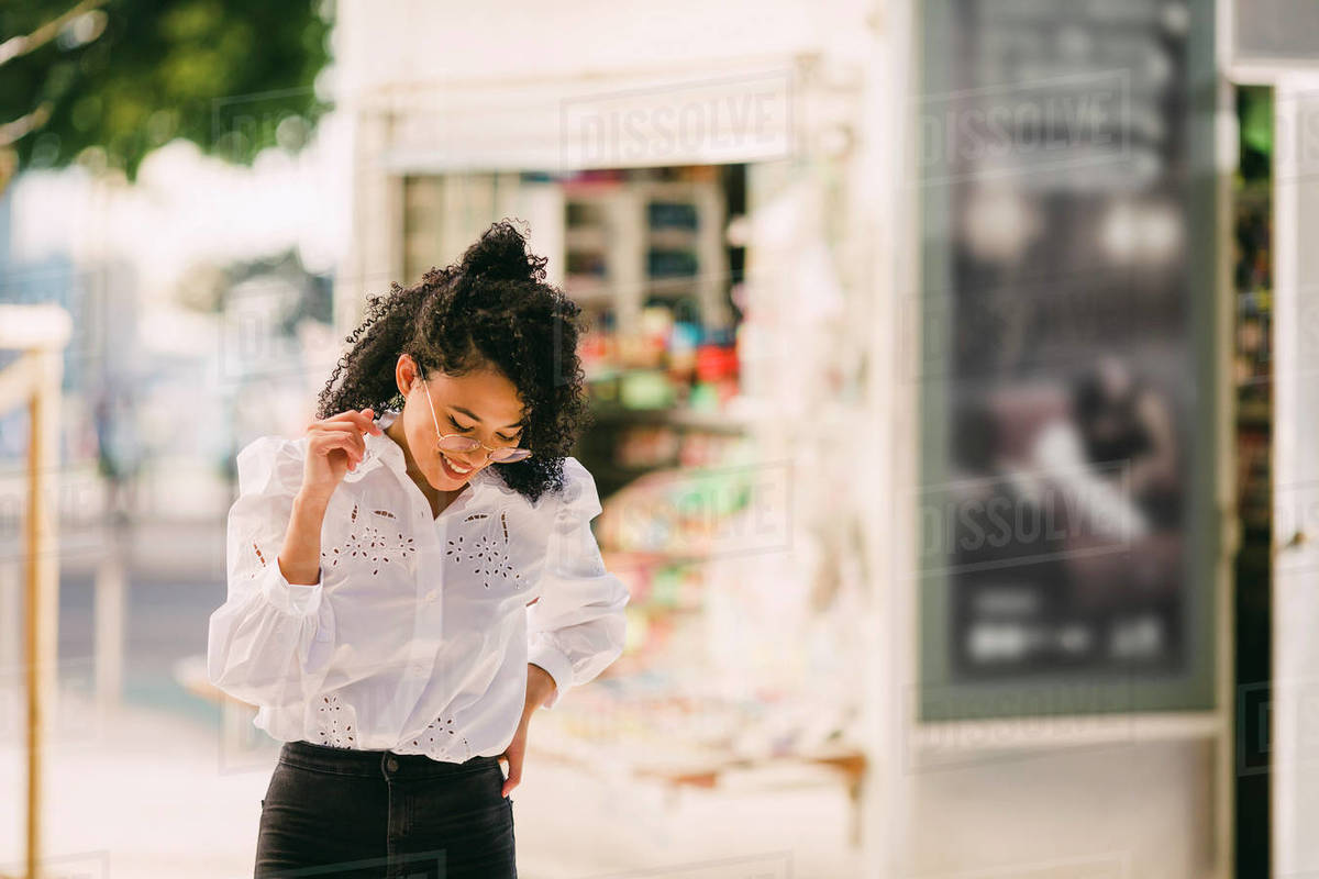 Happy young woman walking on urban sidewalk Royalty-free stock photo