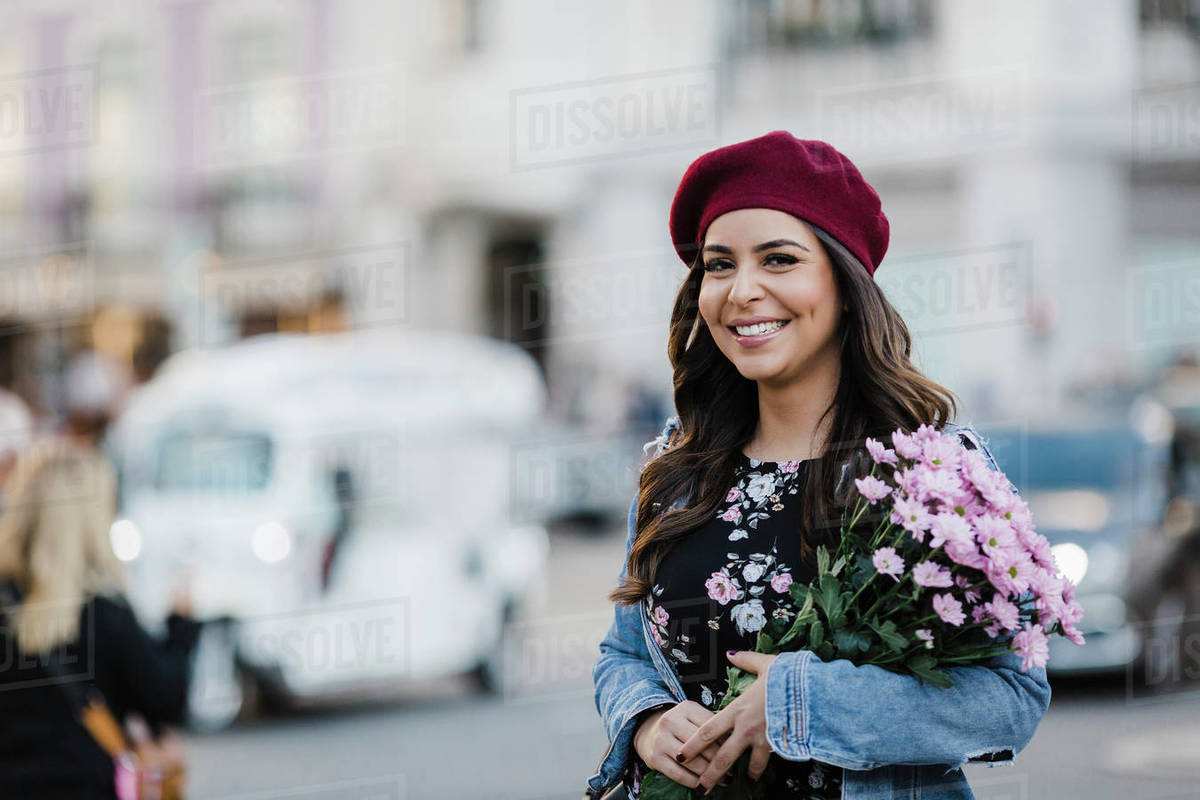 Portrait happy young woman in beret with flower bouquet on urban street Royalty-free stock photo