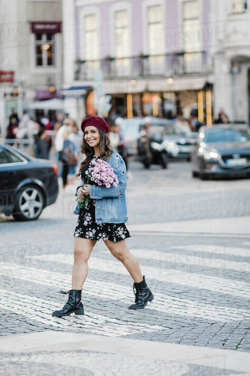 Portrait smiling young woman crossing street with flower bouquet Royalty-free stock photo