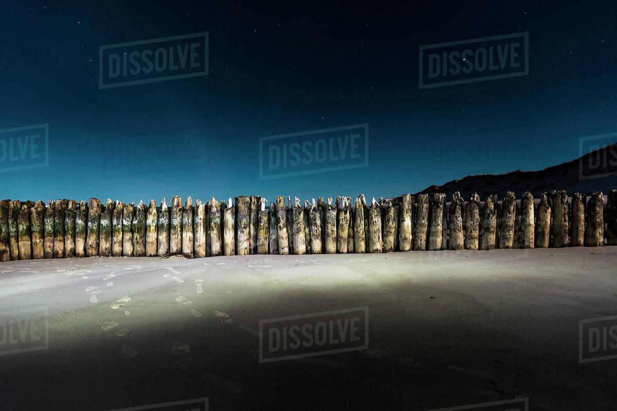 Sheet piling wall illuminated on beach at night Royalty-free stock photo