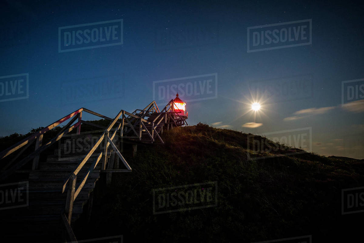 Illuminated lighthouse under full moon night sky, Norddorf, Schleswig Holstein, Germany Royalty-free stock photo