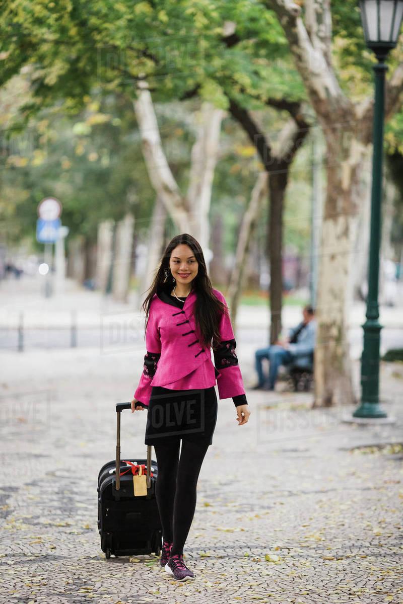 Smiling female tourist pulling suitcase along treelined sidewalk Royalty-free stock photo