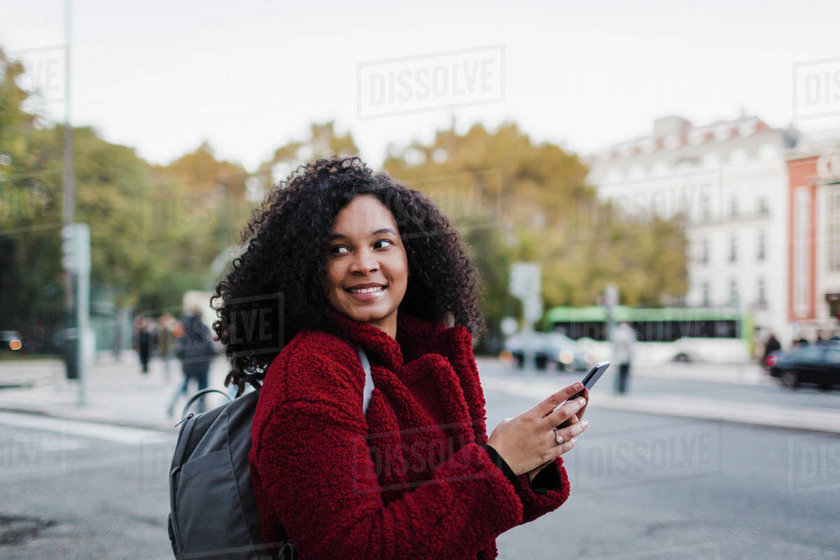 Smiling young woman with smart phone looking over shoulder on city street Royalty-free stock photo