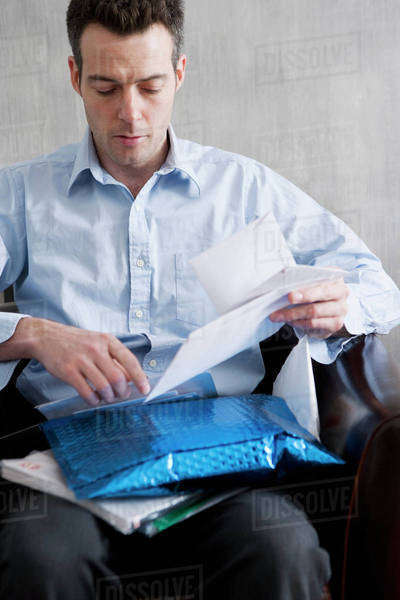 A man sifting through a pile of mail Royalty-free stock photo