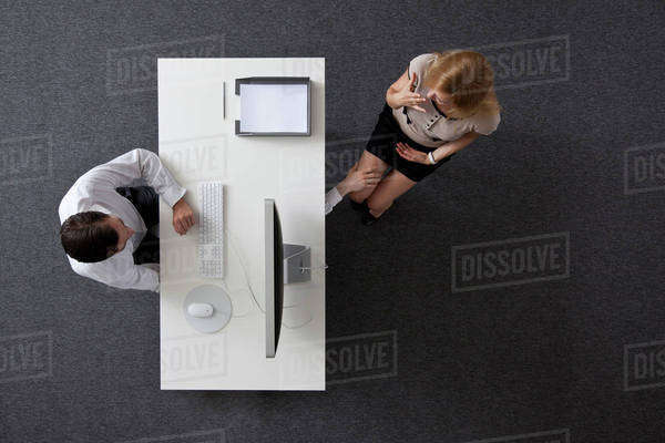 A businessman reaching under a desk to touch a woman's knee, overhead view Royalty-free stock photo