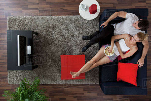 A cheerful couple watching TV and eating popcorn in their living room, overhead view Royalty-free stock photo