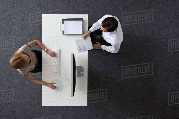 A businessman giving papers to a businesswoman sitting at a desk, overhead view Royalty-free stock photo