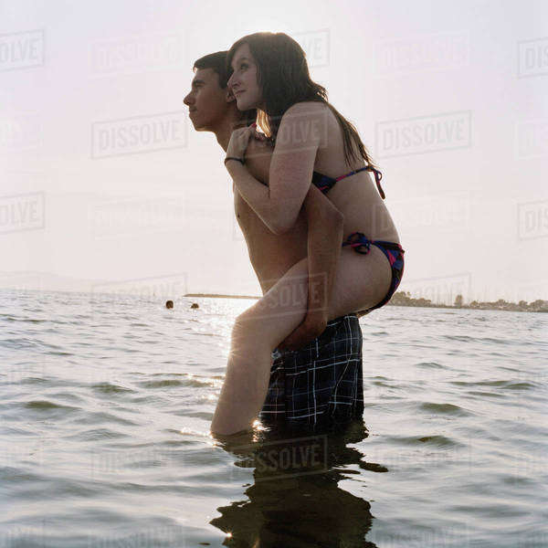 A young man giving his girlfriend a piggyback ride in the sea Royalty-free stock photo
